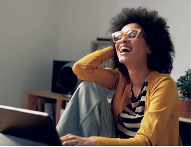 A woman laughs while typing on her laptop